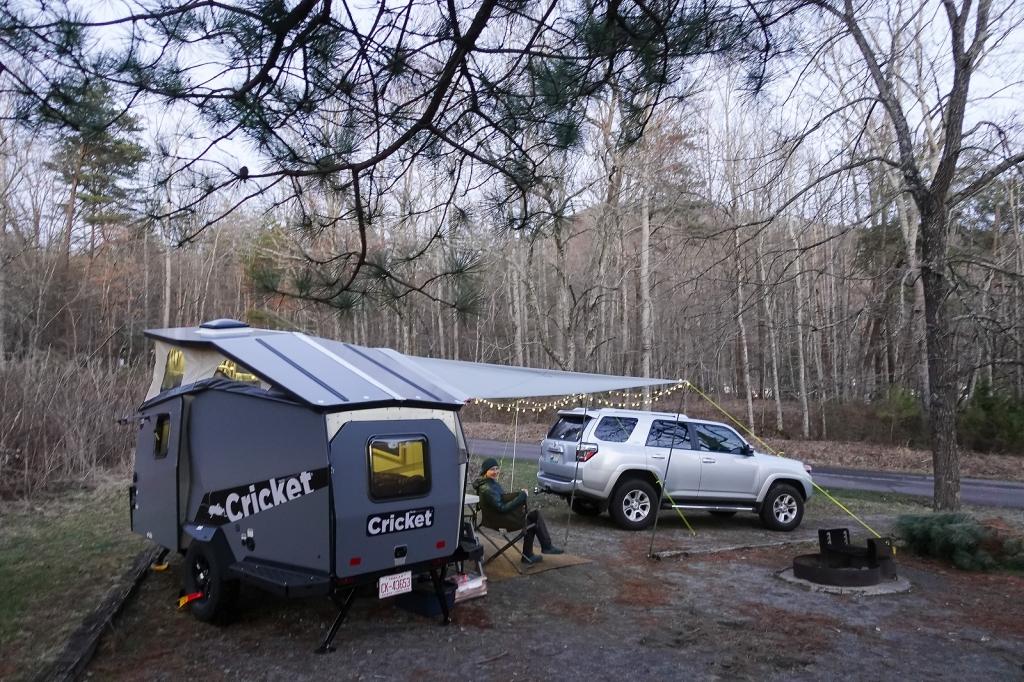 TAXA Cricket camping trailer in camp at dusk.
