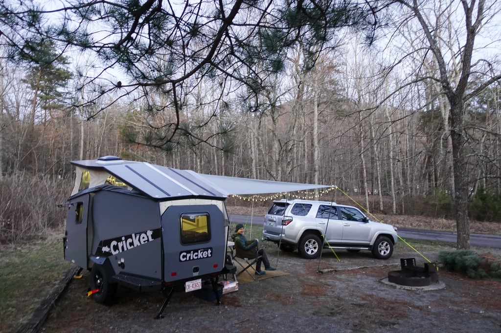 TAXA Cricket camping trailer in camp at dusk.