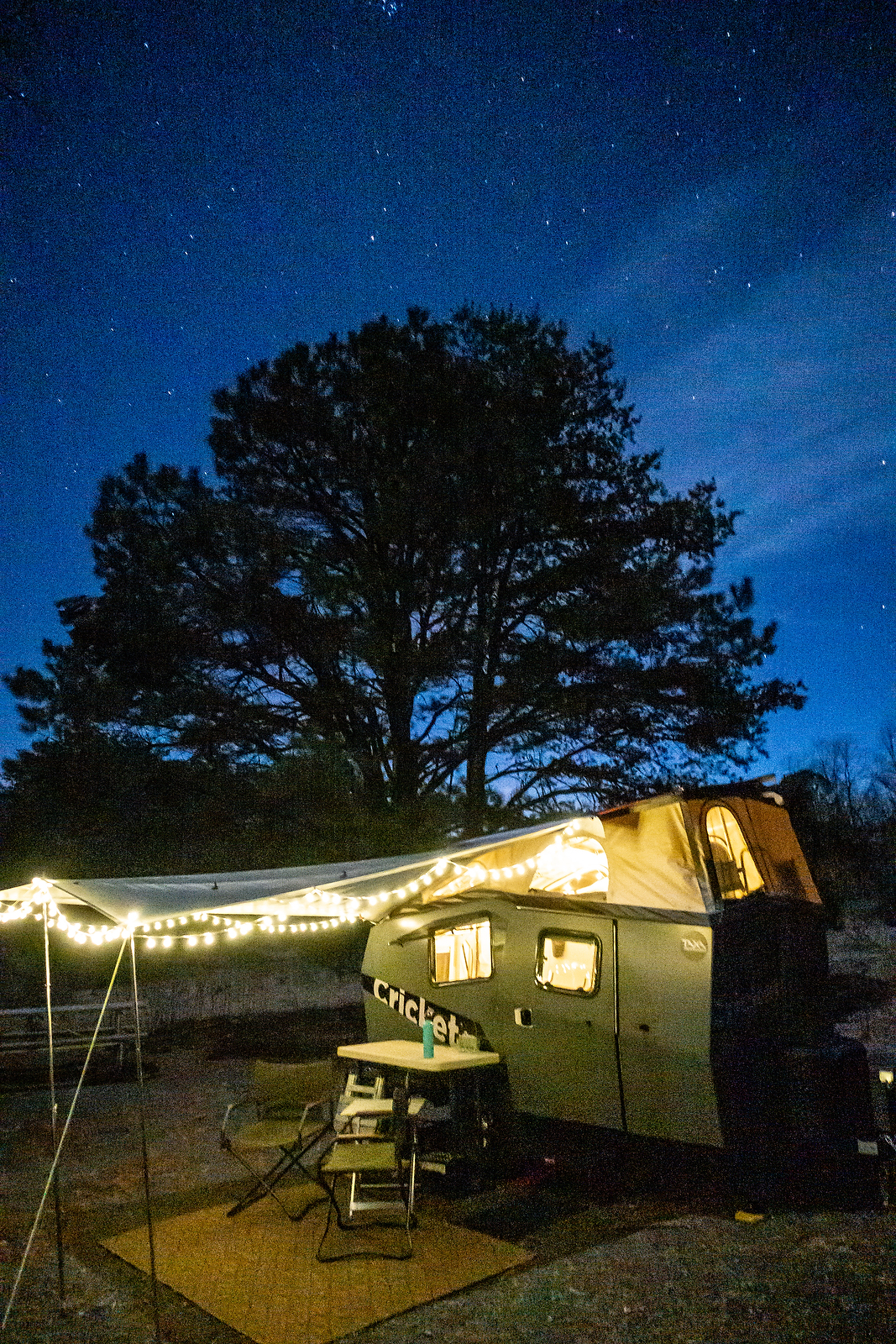 A nighttime view of the camper and stars.